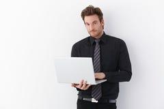 Hombre hermoso con la computadora portátil fotos de archivo