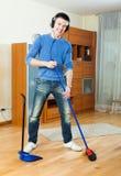 Hombre hermoso con la escoba y el recogedor de polvo en casa Imagen de archivo libre de regalías