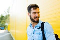 Hombre hermoso con la mochila en amarillo Fotos de archivo