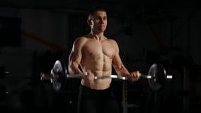 Hombre hermoso con los músculos grandes, presentando en los pesos de elevación del hombre muscular del gimnasio sobre el funciona metrajes