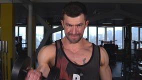 Hombre hermoso con los trenes grandes en el gimnasio, ejercicios de los m?sculos almacen de metraje de vídeo