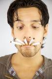 Hombre hermoso con muchos cigarrillos en su boca Imagen de archivo