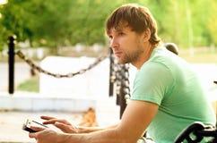 Hombre hermoso con Tablet PC en el parque al aire libre Foto de archivo libre de regalías