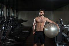 Hombre hermoso con una bola del ejercicio Fotos de archivo libres de regalías