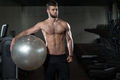 Hombre hermoso con una bola del ejercicio Imagenes de archivo