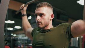 Hombre hermoso concentrado que ejercita sus músculos del pecho y que entrena a sus hombros en el gimnasio Tirado en 4k almacen de metraje de vídeo