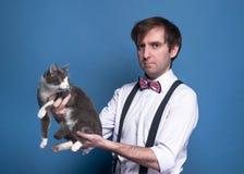 Hombre hermoso confiado en la camisa, la corbata de lazo rosada y la liga sosteniéndose en gato gris lindo de los brazos extendid imágenes de archivo libres de regalías