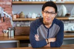 Hombre hermoso confiado que se coloca en café con los brazos cruzados Fotografía de archivo