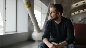 Hombre hermoso de la barba que se sienta en el aeropuerto y la espera para la salida metrajes