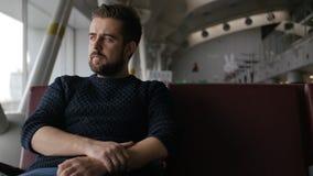 Hombre hermoso de la barba que se sienta en el aeropuerto y la espera para la salida almacen de video