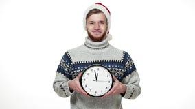 Hombre hermoso de la cámara lenta en el suéter que sostiene el reloj que muestra tiempo a la cámara metrajes