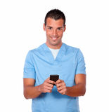 Hombre hermoso de la enfermera que manda un SMS con su teléfono móvil Foto de archivo libre de regalías
