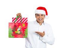 Hombre hermoso de Navidad que sonríe y emocionado sobre su bolso festivo Imagen de archivo