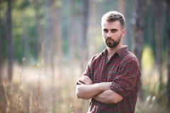 Hombre hermoso del ajuste que presenta en el bosque que lleva la camisa comprobada Foto de archivo libre de regalías