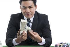 Hombre hermoso del retrato en el traje negro que sostiene pilas de dólares y Imágenes de archivo libres de regalías