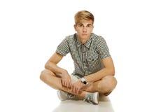 Hombre hermoso del youn que se sienta en el suelo Fotos de archivo libres de regalías