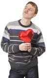 Hombre hermoso divertido joven con el globo rojo del corazón Imagen de archivo libre de regalías