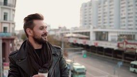 Hombre hermoso elegante feliz con una barba que bebe el café o el té para llevar que mira al lado Imagen de archivo