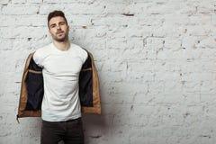 Hombre hermoso en camiseta en blanco que saca su chaqueta de cuero, fondo blanco de pared de ladrillos imagen de archivo