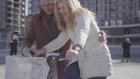 Hombre hermoso en capa marrón que enseña a su novia a montar la bicicleta en la ciudad Ocio de pares hermosos de la ciudad metrajes