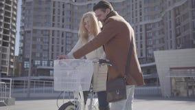 Hombre hermoso en capa marrón que enseña a su novia a montar la bicicleta en la ciudad, risa de la gente Ocio de almacen de metraje de vídeo