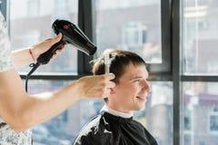 Hombre hermoso en el peluquero que consigue un nuevo corte de pelo foto de archivo