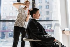 Hombre hermoso en el peluquero que consigue un nuevo corte de pelo imágenes de archivo libres de regalías