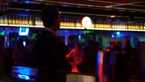 Hombre hermoso en el whisky de consumición del traje y la gente de observación que bailan en club de noche almacen de video