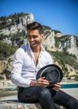 Hombre hermoso en la camisa y el sombrero blancos en la playa Fotografía de archivo