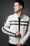 Hombre hermoso en la chaqueta de cuero blanca. Fotos de archivo