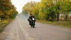 Hombre hermoso en las gafas de sol que montan con su novia en una motocicleta en la carretera de asfalto en bosque en otoño his metrajes