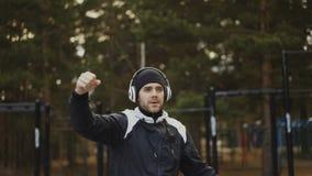 Hombre hermoso en los auriculares que hacen ejercicio del calentamiento mientras que música que escucha en parque del invierno almacen de metraje de vídeo