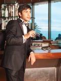 Hombre hermoso en smoking en el vidrio del whisky de la explotación agrícola de la barra Foto de archivo