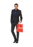 Hombre hermoso en traje con la muestra de la venta Imagenes de archivo