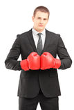 Hombre hermoso en traje negro con la presentación roja de los guantes de boxeo Imagen de archivo