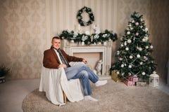 Hombre hermoso en un Año Nuevo de la bufanda de la capa con los regalos Fotografía de archivo