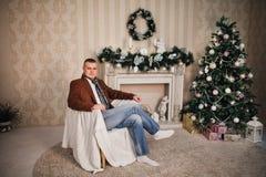 Hombre hermoso en un Año Nuevo de la bufanda de la capa con los regalos Imágenes de archivo libres de regalías
