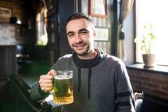 Hombre hermoso en un pub o una barra que sostiene la taza la cerveza alta en el aire para las alegrías Imagen de archivo libre de regalías