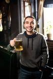 Hombre hermoso en un pub o una barra que sostiene la taza la cerveza alta en el aire para las alegrías Fotos de archivo libres de regalías