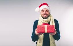 Hombre hermoso en un sombrero de la Navidad que sostiene los regalos en el fondo blanco Fotos de archivo
