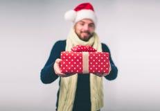 Hombre hermoso en un sombrero de la Navidad que sostiene los regalos en el fondo blanco Fotografía de archivo