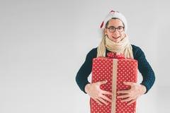 Hombre hermoso en un sombrero y los vidrios de la Navidad que sostienen los regalos en el fondo blanco Imagen de archivo