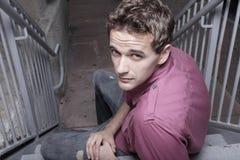Hombre hermoso en una escalera Imágenes de archivo libres de regalías