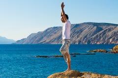 Hombre hermoso en una posición de la yoga respecto a la playa fotografía de archivo libre de regalías