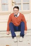 Hombre hermoso enojado con los vidrios y el suéter que asisten en pasos Foto de archivo libre de regalías