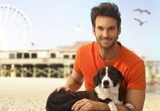 Hombre hermoso feliz con el perro en la playa del paisaje marino Imagenes de archivo