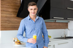 Hombre hermoso feliz con el vidrio de zumo de naranja fresco Fotografía de archivo libre de regalías