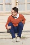 Hombre hermoso feliz con los vidrios y el suéter que asisten en pasos Imágenes de archivo libres de regalías