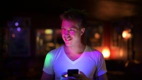 Hombre hermoso feliz joven que piensa mientras que usando el teléfono en el club almacen de metraje de vídeo