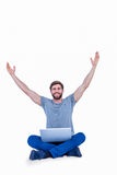 Hombre hermoso feliz que anima detrás de su ordenador Foto de archivo